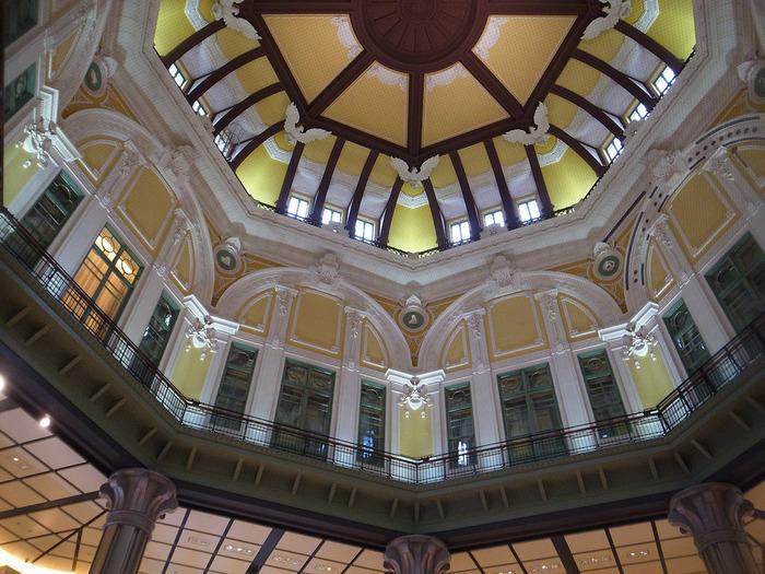 屋根のレリーフ部は、オリジナルのデザインを採用して復元してありますが、1,2階の装飾は、耐震や利便を考慮し、オリジナルを尊重しつつも、現代の素材を用いて設計施工されています。  【ドーム上部、八方向に設置された窓から差し込む光によって、レリーフの凹凸と、当時そのままに再現した色調が映えて、実に優雅な空間を生み出している。】
