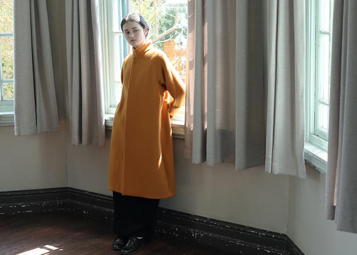 光にきれいに映えるオレンジ色のコートは、ブラウンの延長として着やすいカラーです。黒いワイドパンツと合わせてシックに着こなしましょう。
