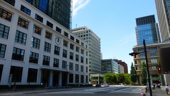"""「丸の内」エリアは、オフィス街といっても""""八重洲""""とは趣きが異なります。 皇居外濠へと続く空間は広々として、ダイナミック。首都・東京ならではの、歴史と威厳、風格ある雰囲気が楽しめる地域です。  【手前は「KITTE」が入る、旧東京中央郵便局跡地に建てられた「JPタワー」。タワーの下層部の白色の外壁は、旧東京中央郵便局の時代に使われていたもの。】"""