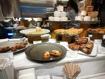 当店は、日本の素晴らしいものを丸の内から世界へと発信するピエール・エルメのコンセプトショップ。  店内には、日本各地の優れた生産者とのコラボした食料品や雑貨、オリジナル商品が並ぶ他、カフェも併設されています。 【デリやスウィーツが並ぶ店内キッチンカウンター】