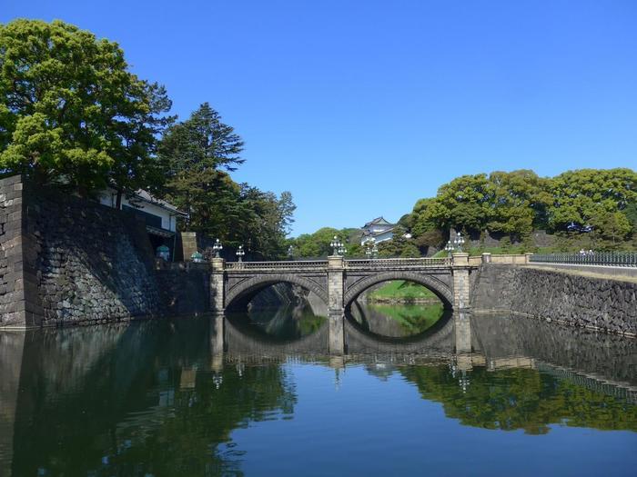 現在の「丸の内」は、日本の経済を牽引する大手企業が集まる日本屈指のビジネス街ですが、幕府が開かれていた江戸期には、その名が示すように当地は、江戸城(皇居)内にあり、大名屋敷が建ち並ぶ武家屋敷街でした。  【「皇居前広場」からの眺め。左が皇居正門、正面は二重橋(正門鉄橋)、奥にのぞくのは、伏見櫓。東京観光の名所の一つであるこの場所は、近代前の江戸城の風情が色濃く残る場所。「皇居前広場」へは、丸の内中央口から行幸通りを歩いて13分程。】