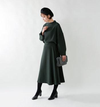 深みのあるグリーンのフレアスカートに、同色のトップスを合わせたセットアップ風コーデ。黒のタイツとパンプスを合わせて、足元をキュッと引き締める効果をプラスしています。 冬らしさを感じさせるベレー帽も、シンプルコーデの良いアクセントになっていますね。