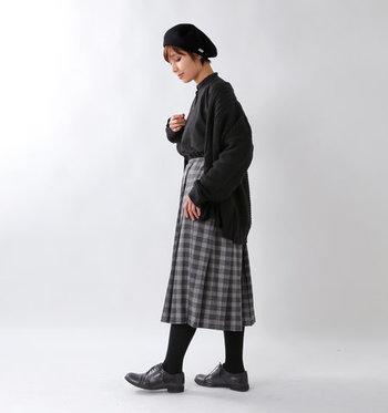 グレーベースのチェック柄プリーツスカートは、黒のブラウスとカーディガンを合わせて、ダークトンでまとめたコーデに。カジュアルになりやすいチェック柄を、大人味に着こなしています。