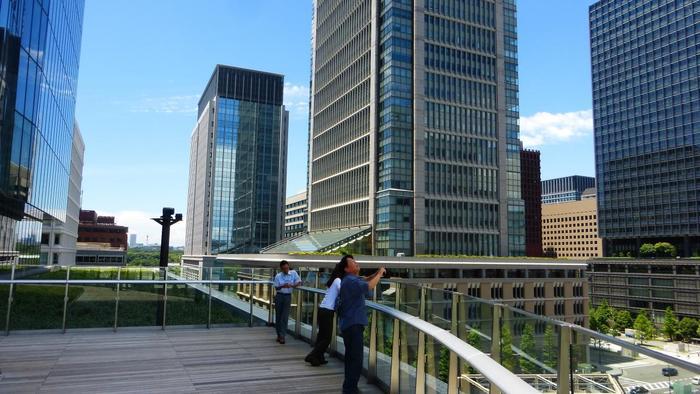 """現在に至っても、三菱UFJ信託銀行や三菱商事、三菱電機や日本郵船といった三菱グループの本社や支社が当地に置かれ、三菱グループ所有のオフィスビルが集中しているように、ここ""""丸の内""""は、今も昔も""""三菱村""""です。  グループ先導による再開発の歩みは、現在進行形でとどまることなく、古き良き時代の遺産と文化を保全しながら、時代をもリードするように日々新しい街が創造されています。  【「KITTE」の6Fは、周囲の景色が眺められる屋上庭園「KITTE GARDEN」になっている。正面が「丸ビル」、その奥が「三菱商事ビル」。】"""