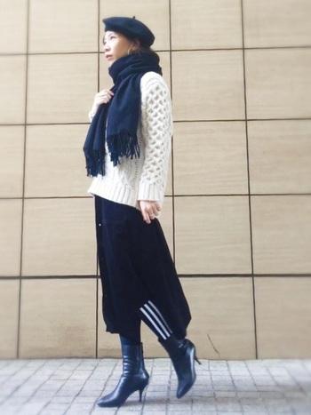黒の変形スカートのインナーに合わせたレギンスラインパンツ。足元は、ショートブーツとボトムスを黒で統一することで、さりげなくラインパンツを全体に馴染ませています。
