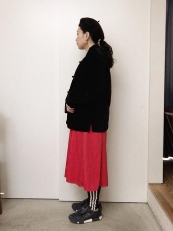 鮮やかな赤のスカートスタイルにタイトなレギンスパンツを合わせたコーデ。下から少しだけ覗く白のラインが、コーデのポイントを作っています。
