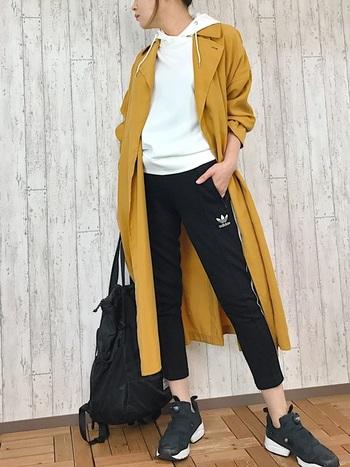 白パーカー×黒ラインパンツのスポーティーな組み合わせに、マスタードカラーのトレンチコートを羽織っています。キレイめのライトアウターを一枚派折ることで、スタイリッシュな大人の着こなしに。