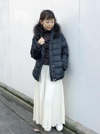 冬によく映える真っ白なプリーツスカートには、黒のダウンを重ねてヘルシーな装いに。ロング丈のスカートが重たくならないようにスニーカーはあえて同色の白を合わせて。