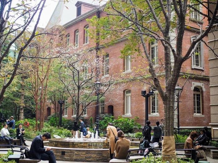 """コの字型の美術館の内側、「丸の内パークビル」と「ブリックスクエア」に挟まれた「一号館広場」は、""""丸の内""""の憩いの場。"""