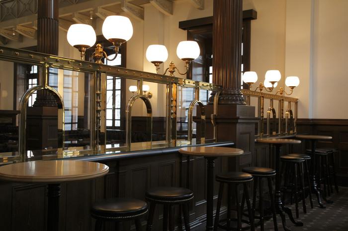 「Cafe 1894」は、三菱一号館の創建当時に銀行営業室として使われていた空間を、忠実に復元したカフェ・バーです。 【画像は、明治期に銀行で使われていた窓口を、照明も含めて細部にわたり再現した、カフェの間仕切り。】