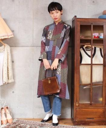 70年代ファッションは、どこかハンドメイド感があることもポイント。パッチワーク風のプリントシャツワンピースに、ヴィンテージ風バッグと大ぶりピアスを合わせたレトロシックなコーディネートです。