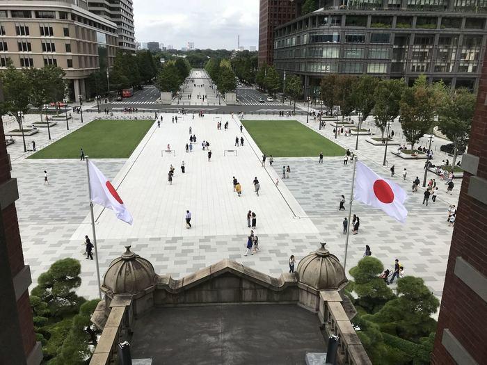 """""""八重洲""""の反対側、皇居外苑と駅に挟まれた地域が、今記事で取り上げる""""丸の内""""です。  【東京ステーションホテル(丸の内駅舎内)の「*アトリウム」から撮影された「丸の内駅前中央広場」と「行幸通り」。左右に建つのは「丸ビル」と「新丸ビル」(「*アトリウム」は、丸の内駅舎中央部の上層にあたり、1階は駅舎の「皇室専用貴賓出入口」となっている。)】"""