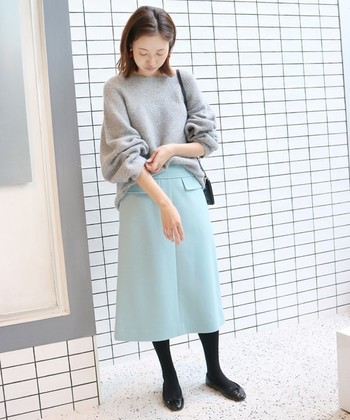 サックスブルーのAラインスカートに、グレーのニットと黒タイツを合わせたコーディネートです。シューズも黒で合わせることで、スカートのキレイめカラーを引き締めつつ、脚長効果も期待できます◎
