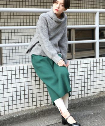 グリーンのタイトなロングスカートに、ベージュのレギンスを合わせたコーディネートです。トップスはグレーのゆったりタートルニットをチョイスして、大人のレイヤードコーデに仕上げています。