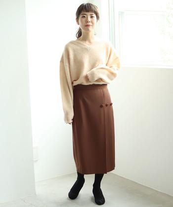 タイトなシルエットの茶色スカートに、ベージュ系のふわふわVネックニットを合わせたコーディネートです。ベーシックカラーの組み合わせなので、黒のタイツがしっかり馴染んで一体感のある着こなしに。