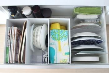 キッチンボードの一番下の引出しは、たっぷり入るのは良いものの意外に使いにくい場所のひとつ。  こちらのお宅では、無印のファイルボックス(ワイド)を仕切りとして活用しています。調理器具や料理本などもすっきり収まり無駄がないですね。