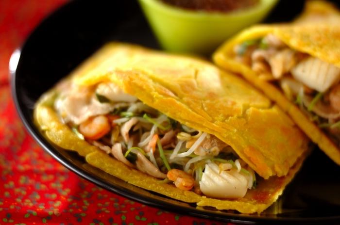 ベトナム風お好み焼きのバインセオ。日本のお好み焼きとは違い、パリっとした生地に豚バラ肉、シーフードミックス、モヤシ、豆苗などをたっぷり挟み、最後にサニーレタスで巻いていただきます。野菜をたっぷり食べられるヘルシーさも嬉しい一品です。