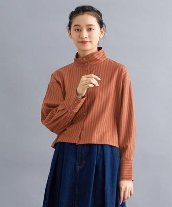 ブラウンがかったオレンジの同系色の縞模様シャツ。ショート丈が少しレトロな雰囲気に。他にもハイネックやカフスなど、さりげないこだわりを感じられる一枚です。