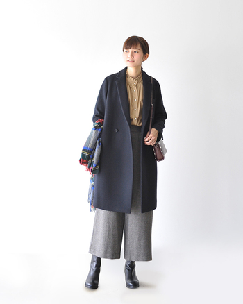 クラシカルなチェスターコートの下に、フェミニンなシャツを合わせた着こなし。  足元のブーツとアクセントとなるチェック柄の大判ストールが、「首」を温めてくれますね。