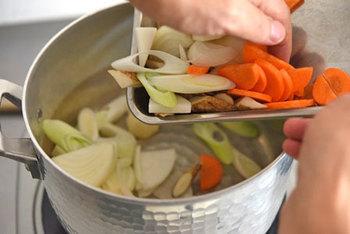 熱したお鍋にごま油を少量入れ、野菜から投入。 そのあと、野菜の上に豚肉をほぐしながら入れると、なべ底に豚肉がくっつくのを防げますよ。
