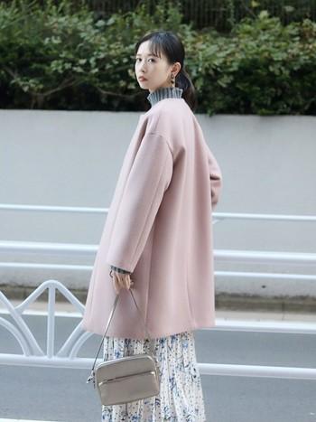 優しい印象の淡いピンクのノーカラーコートに、あえて小花柄のスカートをあわせて甘めにコーディネート。だけど甘さ100%にならないのはニットのリブが大きめ&ダークカラーであること、大ぶりの耳飾りやシンプルなバッグを巧みに組み合わせた結果なのです。