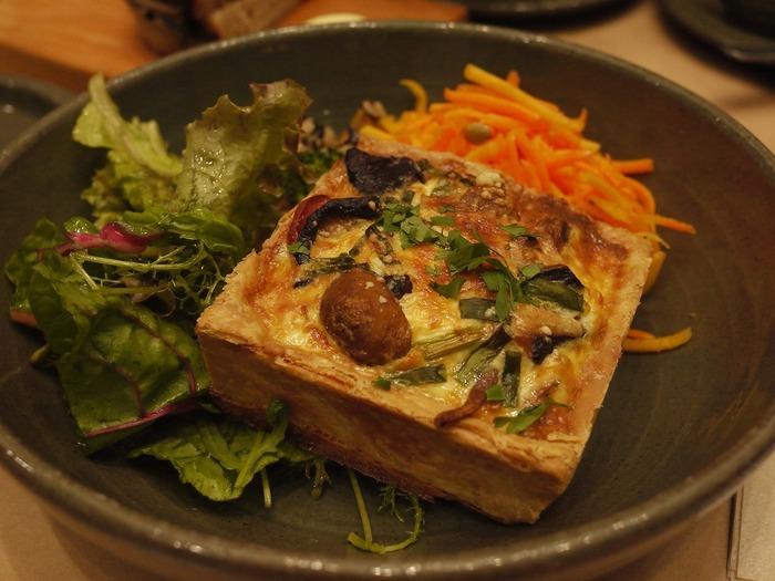 """「ローズベーカリー」は、パリで誕生した""""英国スタイル""""のDELIカフェです。  BIO食材を用いたオリジナルのデリやデザートは、ヘルシーであるばかりでなく、美味しいと評判。特に人気なのが『デリの盛り合わせ』と、ボリューミィで具材がたっぷり入った『キッシュ』。他にも、スープや煮込み料理もあり、どの料理を頼んでも、グリーンサラダと人気の「パン・ド・カンパーニュ」(おかわり自由)で付いてきます。【『キッシュと野菜の2種類添え』】"""