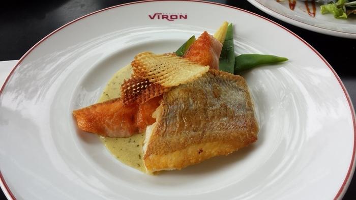 """「VIRON」は、設えや雰囲気だけでなく、皿の中身も本場そのもの。料理もデザートも美味!と評判です。ランチ、カフェ、ディナーと、シーン様々に、「VIRON」ならではの食事やカフェが楽しめます。  【渋谷店は『VIRONの朝食』が有名だが、丸の内店はランチがとりわけて人気。魚や肉、サラダといった""""本日のメインディッシュ""""に、人気のバゲット(食べ放題)が付いた『ランチ』がリーズナブルに楽しめる。(画像は、平日のメインディッシュ『鮮魚のポワレ』)】"""