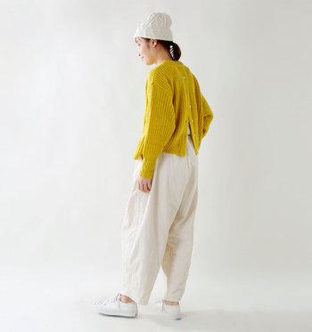 白のニット帽×白のワイドパンツに、イエローのカーディガンを合わせたスタイリングです。前後どちらを前にしてもOKな2way仕様カーディガンなら、着こなしの幅もグッと広がりますよ。