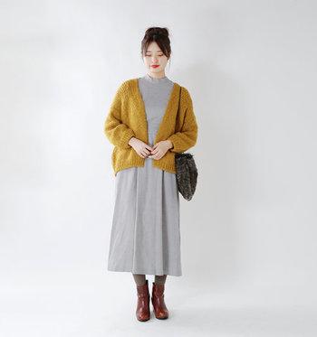 グレーのシンプルワンピースに、マスタード色のカーディガンと茶色のショートブーツを合わせたコーディネート。柔らかさと清楚さを兼ね備えた着こなしは、女性らしくきちんとキメたい場面にもぴったりです。