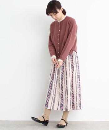 柔らかな印象のくすみピンクカーディガンに、柄スカートに合わせたコーディネートです。着こなしが難しい柄物スカートでも、シンプルなカーディガンなら上手に着こなせます。襟からインナーの白をちら見せして、大人ガーリーなコーディネートに仕上げて。