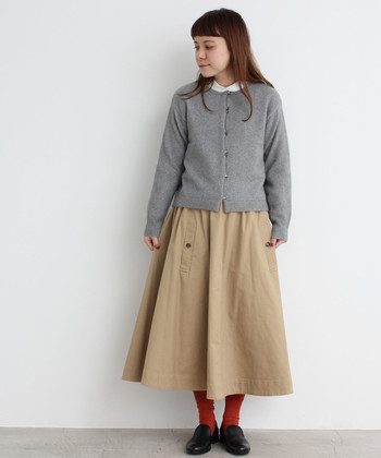 グレーのカーディガンにベージュのフレアスカートを合わせた、ナチュラルなコーディネートです。インナーのブラウスの襟をちらりと覗かせた首元が、シンプルになり過ぎないワンポイントに。赤の靴下も、ナチュラルコーデのいい差し色になっています。