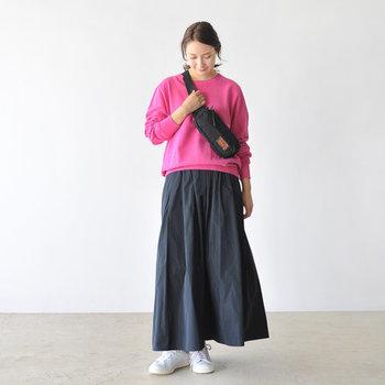 小ぶりな黒のウエストバッグを、パッと目を惹くピンクトップスに合わせたコーディネート。ボトムスにはロングスカートをチョイスして、カジュアルになり過ぎない着こなしに仕上げています。