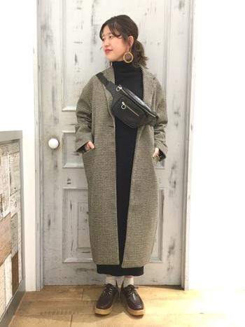 チェック柄のコートにワンピースを合わせたナチュラルコーデは、ウエストバッグを斜めがけにすることでワンアクセントをプラス。黒のレザー小物を合わせる着こなしは、大人っぽく仕上がりますね。