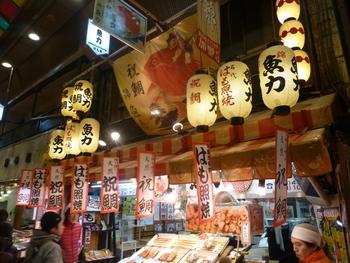 提灯や垂れ幕などのにぎやかな飾り付けが目を引くのは、焼き魚専門店の【魚力】。様々なお魚が並べられた店先は、市場らしい活気に溢れています。