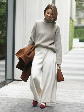 ゆったりとしたワイドパンツの裾からちらりと見える足の甲がお洒落な雰囲気を醸し出しています。たっぷりとした布地のアレンジで、暖かく見えます。
