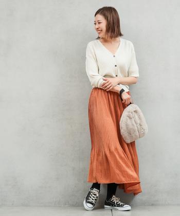見ているだけで温かくなるような色合いのパッキリとした淡オレンジは、白ニットと紅茶色の優しいファーバッグを合わせて見た目にも心地いいコーディネートに。