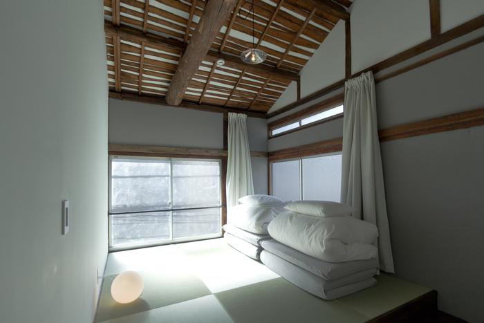 """宿泊する部屋の内部は、古い建物の梁をそのまま使用し、白を基調としたシンプルな空間になっています。お部屋によって異なるすりガラスの模様が室名になっているなど、至る所にリノベーションの痕跡を感じられます。そんな""""和モダン""""な雰囲気も、海外からの観光客に人気の理由のひとつです。"""