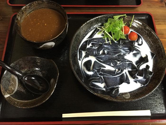 代表するメニューのひとつが「黒帯」です。竹炭を練り込んだ真っ黒なひもかわうどんが豆乳スープに入っていて、その見た目に驚きます。お出汁の効いたキーマカレーつゆと豆乳のまろやかさが、絶妙なハーモニーを奏でます。竹炭入りのひもかわうどんが食べられるのは、ここだけとあって、これを目当てに訪れるお客さんも多いんだとか。