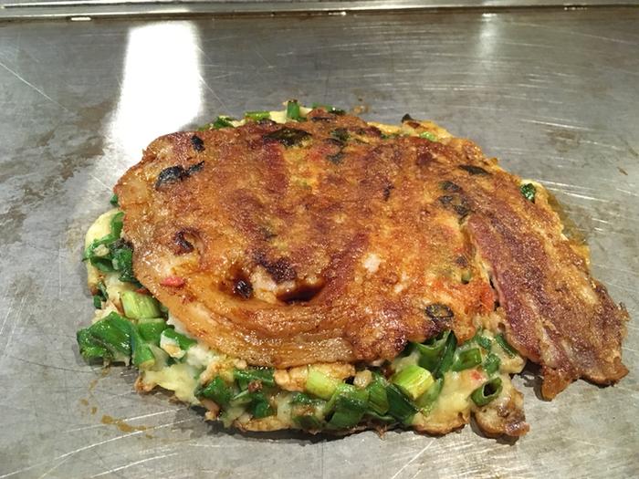 こちらは「福太郎本店」の看板メニューで、一番人気の「豚ねぎ焼き」。ベテランが職人技で丁寧に焼き上げてくれるのも魅力です。豚ねぎ焼きは主に鹿児島産の最高級の豚肉と、大阪産の青ネギを使用しています。大阪というと、青ネギのイメージがあまりないと思いますが、実は大阪では昔、青ネギがたくさん栽培されていて青ネギの名産地として知られていたのです。そんな自家製の醤油ダレで味わう大阪産青ネギをふんだんに使用した豚ねぎ焼きは、生地と絶妙なハーモニーを奏でいます。そのため、一口食べればおいしくて幸せな気持ちになれます。
