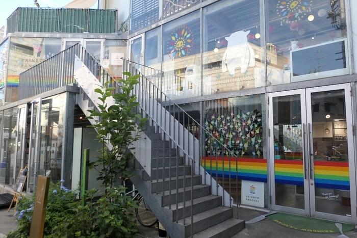 「レインボーパンケーキ(RAINBOW PANCAKE)」は、表参道駅のA2出口から徒歩約8分、明治神宮前駅の5番出口からは徒歩約3分のところにあるお店です。ハワイで虹は幸せの象徴なのだそう。虹と同じくハワイの人たちを笑顔にするパンケーキを日本にも届けたい、という想いがこめられたお店。外観はユニークで楽しいデザイン♪入口の足元にも注目してみてくださいね。