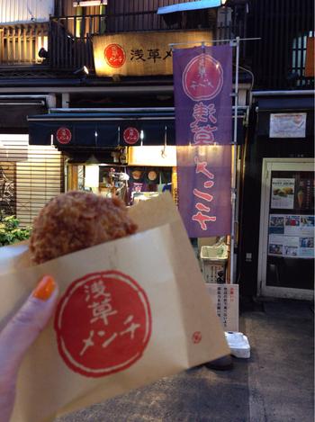 伝法院通りの中でもひときわ目立つ人気店が、こちらの「浅草メンチ」です。赤い丸のハンコ風ロゴが目印。 甘味が多い浅草において、甘いものが苦手な人でも楽しめるスポットでもあります。