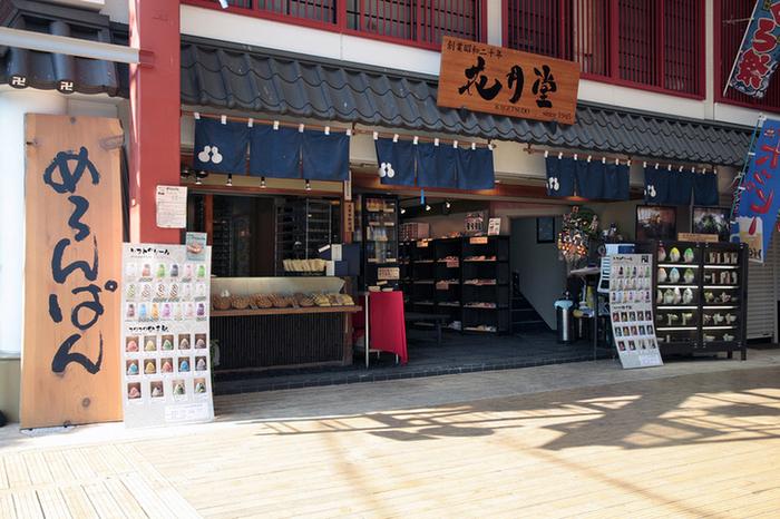 """大きな""""めろんぱん""""の立て看板が目を引く「浅草花月堂本店」さん。見ての通りメロンパンが有名で、和風の食べ歩きグルメが多い浅草で異彩を放つお店です。仲見世通りを抜けたら浅草寺本堂前を左に曲がり、しばらく進んだところにある「西参道商店街」の角に見えてきます。 目立つ位置にお店を構えていることもあってか、平日昼間でも行列ができる人気店。休日なら売り切れ覚悟のお店なので、なるべく日中の早い時間に行くことを推奨します!"""
