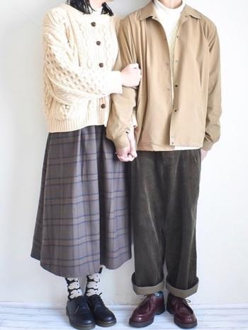 女性はケーブル編みのカーディガン、男性は同じくケーブル編みのセーター。パッと見ただけで分からないさり気なさが素敵♪