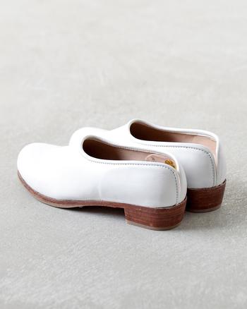 """ドイツ語で""""本という意味の""""buch""""を文字遊びで並べた「hcubuch」の靴は、まるでお気に入りの本を開くような高揚感で履くことができる1足です。 こちらのシューズはぷっくりしたフォルムが可愛らしいサボシューズ。丁寧に仕立てあげられたフチが描く曲線が上品かつユニークなデザインで素敵です。「すずめ」という名前も可愛い!"""
