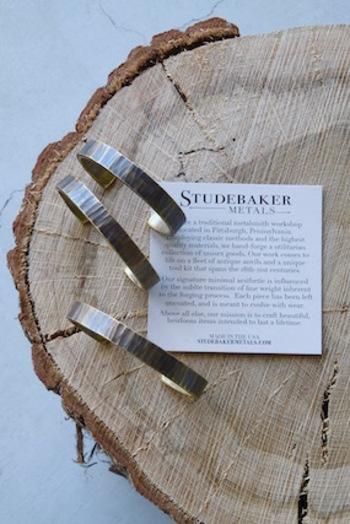 """こちらはアメリカ発のアクセサリーブランド、『STUDEBAKER METALS(スチュードベイカー メタルズ)』の真鍮製のバングルです。一点一点、ハンマーで丹念に叩き上げて製作するバングルは、独特の味わい深い立体模様が特徴的。ポリッシュやコーティングをかけずに""""Work Patina""""という仕上げを施しているため、真鍮の美しい経年変化を楽しむことができます。(写真のバングルは幅10㎜の「BASSEMER CUFF」)"""