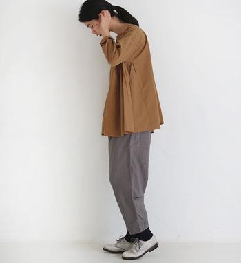 ゆるっと履けるワイドパンツは、足元からタイツやレギンスを覗かせて今っぽいコーディネートが楽しんで。キャメルカラーのトップスを合わせて、グレーのワイドパンツを季節感たっぷりにコーディネートしています。