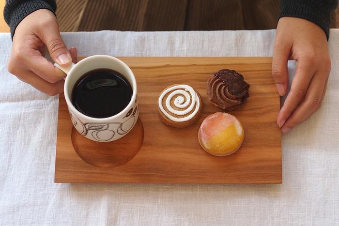 カップを置けるくぼみの付いた木のトレイは、コーヒーとお菓子をのせたり、トレイなのにそのままお皿として活用できる一石二鳥な便利アイテムです。また、仕上げ剤は口に入っても問題のない、蜂の巣のロウである蜜蝋と食材でもある荏胡麻の油を混ぜ練り上げた「みつろう塗料」を使用しているので安心♪乾燥が気になり始めたら、オリーブオイルなどの植物性オイルを布に含ませ塗ってください。それだけでぐっと長持ちします。