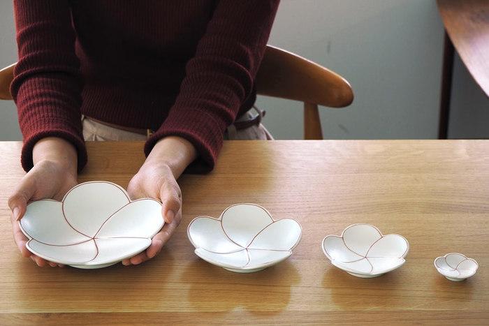 日本の磁器発祥の地・佐賀県有田でも貴重な窯元のひとつと言われている「幸楽窯」。そんな幸楽窯が伝統ある有田焼に遊び心と吉祥のエッセンスを取り入れて作ったのが、お花の花びらがふわりと舞い降りたようなこちらのお皿。和菓子をのせて使いたくなりますよね。ちょこっとお煎餅やあられをのせたり、ときにはチョコレートをのせたり。そしておめでたい席にもピッタリだったりと、様々な使い方ができそう。