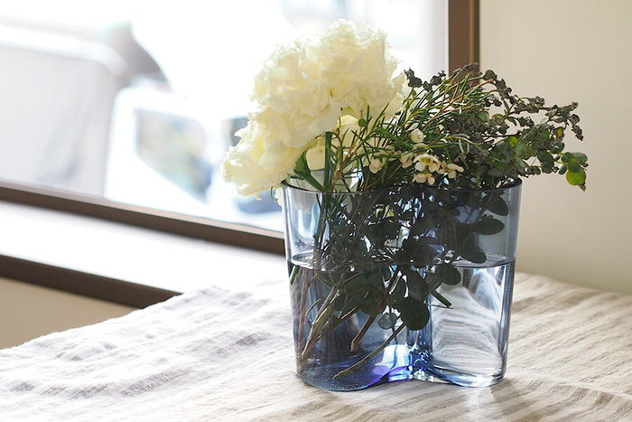 建築家アルヴァ・アアルトがフィンランドの湖からインスピレーションを受け、2014年の新色「レイン(雨)」を発表。ブランドの特徴でもある曲線が流れるように美しい花瓶は、小花だけでなくイングリッシュローズや百合などの大輪の花もしっかりと受け止めてくれる頼もしさも併せ持っています。グラスの透き通ったブルーグレーカラーが植物を生き生きと見せてくれて、シーズン問わずインテリアにすっと馴染むので、季節ごとにどのお花を活けようか考えるのも楽しみになりますね。