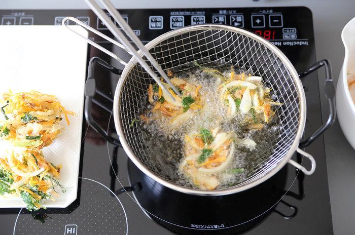 そして、お玉に少量のたねをのせて鍋のヘリから静かに油に落とすと、分解せずにきれいに揚がります。油の温度は170℃。初心者の方は、写真のような揚げ網付きの鍋もいいかもしれませんね。